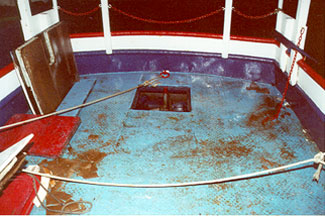 Photo 2 - Aft end of main deck showing intact steel bulwark and hatch opening in main deck with no sealing gasket or means of securing flush wooden cover