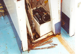 Photo 9 - Disintegration due to dry rot of door frame and console base, and corrosion in way of irregularly shaped hole in main deck